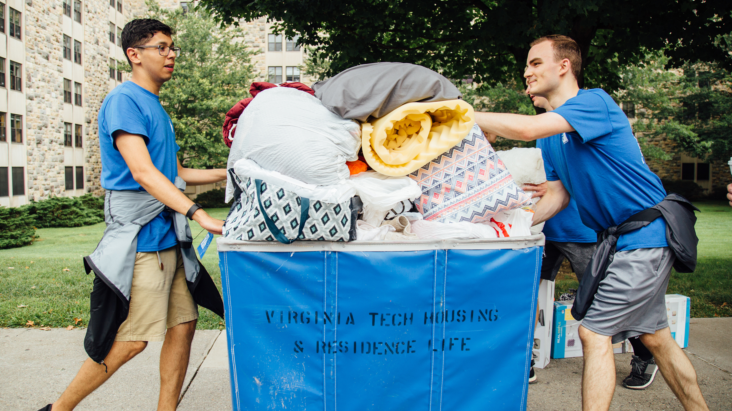Two helpers push a cart as part of move in day at Virginia Tech