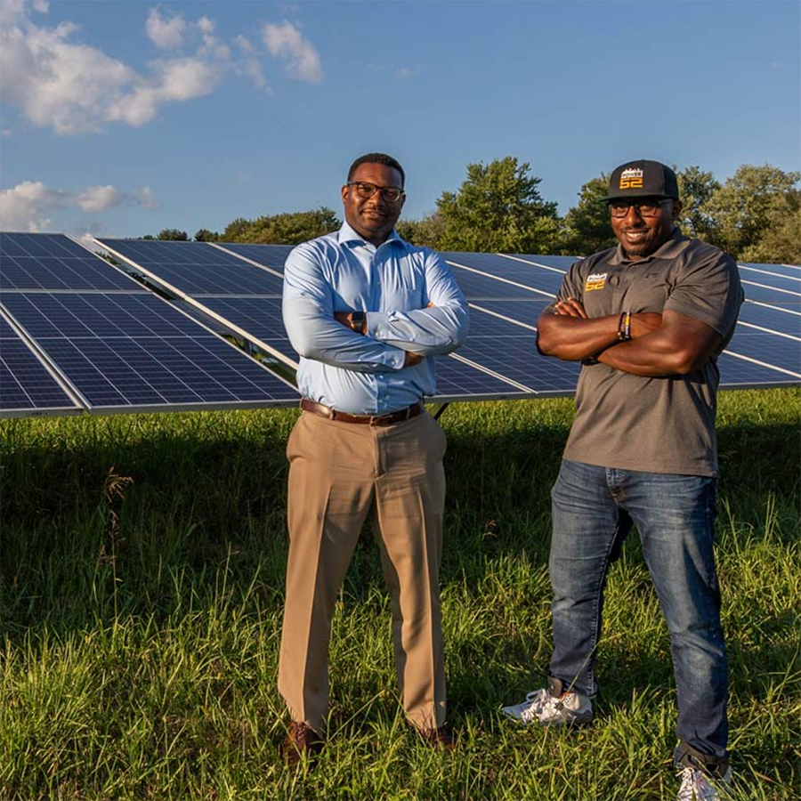 Two alumni stand in a field of solar panels