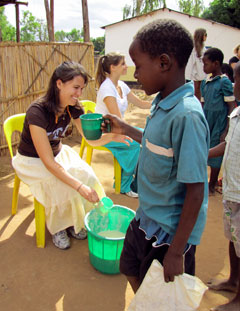 Student Lauren Scheid hands a cup of nsima to a child during a feeding program at Malemia Primary School.