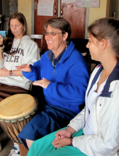 Kristen Haley, a senior human development major from Glen Allen, Va.; Jean Elliott, communications manager for the College of Liberal Art and Human Sciences; and Becca FitzGerald, a sophomore human development major from Chesapeake, Va., receive a drumming lesson.