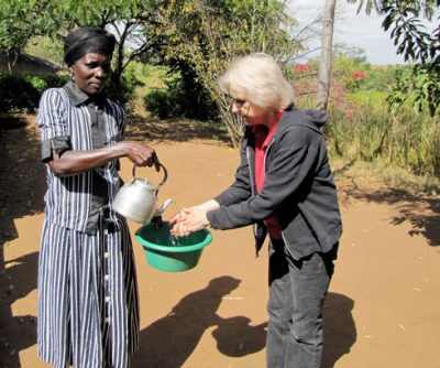 Patricia Kelly, a professor in the School of Education, completes a proffered handwashing before eating at Freedom Gardens.