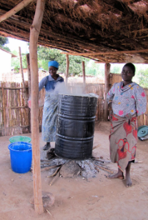 Women from nearby villages oversee the cooking of nsima for the feeding program, heating the corn porridge in a 55-gallon drum over a fire.