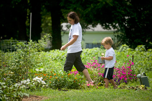 Gardens Growing Families participants Laurel Cosby and son Ivan water their garden plot.