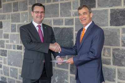 Kevin Lane (left), a principal at Deloitte and Virginia Tech alumnus in accounting, hands over the Deloitte Foundation's matching gift agreement to and shakes hands with Charlie Phlegar, vice president for advancement at Virginia Tech.