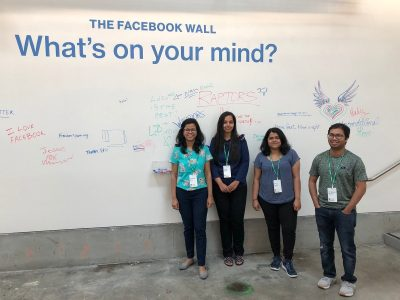 Tanushree Mitra and her students standing in front of The Facebook Wall