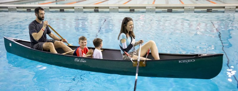 Family in a canoe with mother with one arm testing an assistive oar