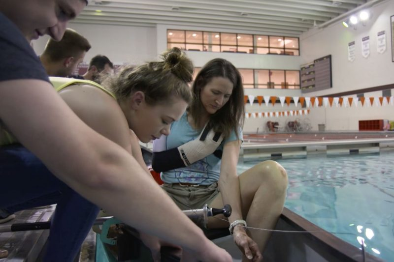 several students seated next to a pool working on a assistive technology for disabled boaters