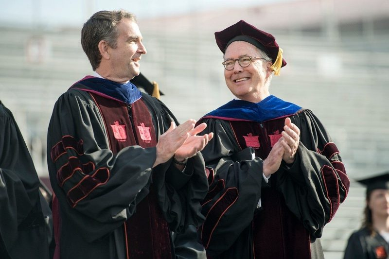 Two men wearing commencement regalia smile and clap.