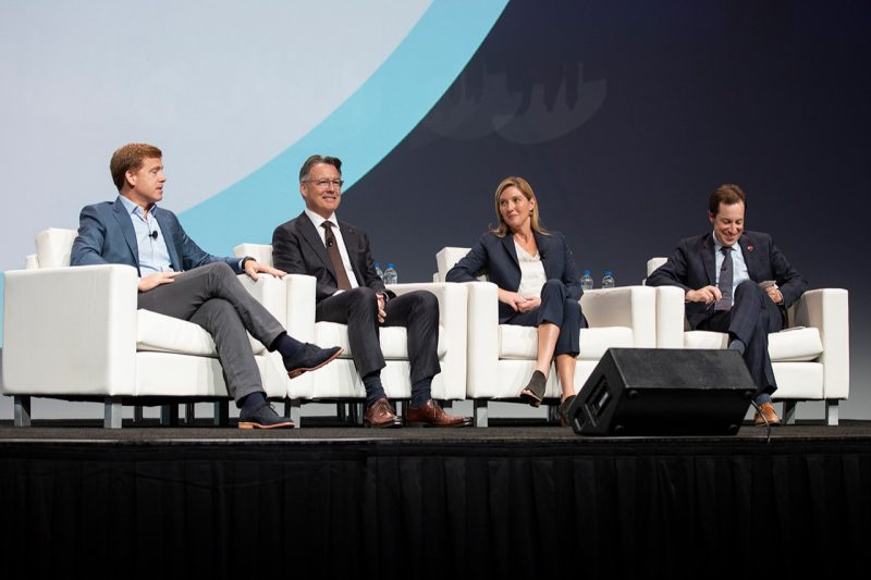 Four people on a stage at a conference for urban development