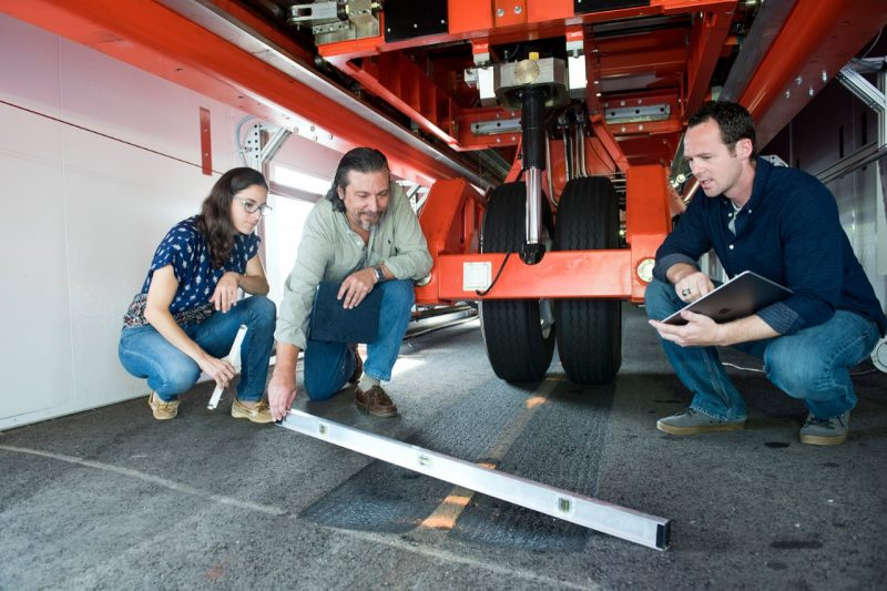 Researchers under a vehicle