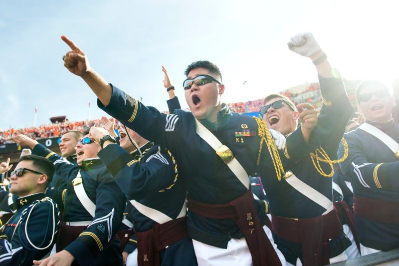 Members of the Corps of Cadets cheer during a football game